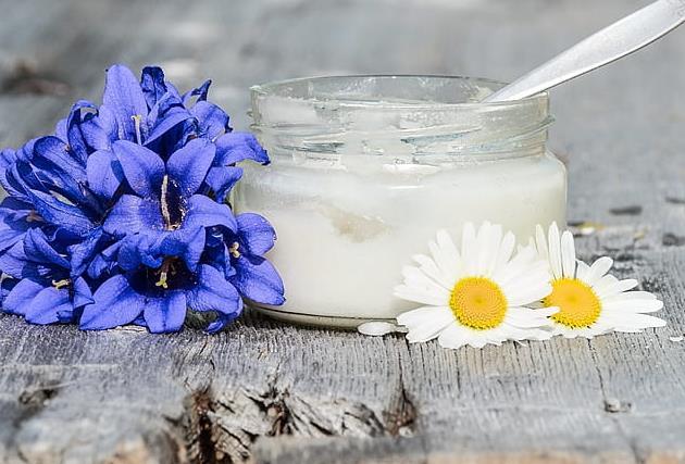椰子油油白色玻璃罐天然健康成分食品药物营养健康胖花木勺两个紫色花瓣旁边的容器 洋甘菊,椰子油